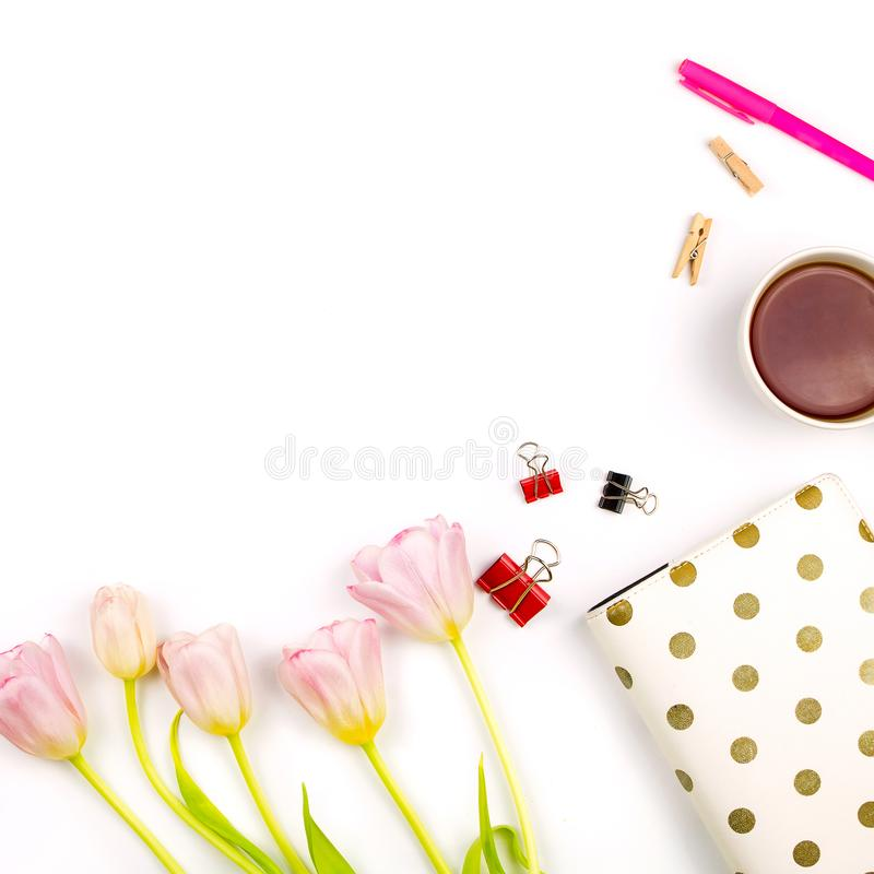 Flatlay with pink tulips, a laptop, cup of tea and other accessories stock photo