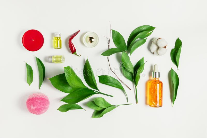 Flatlay of serum, perfume, bath bomb, essential oils with ruscus leaves royalty free stock photo