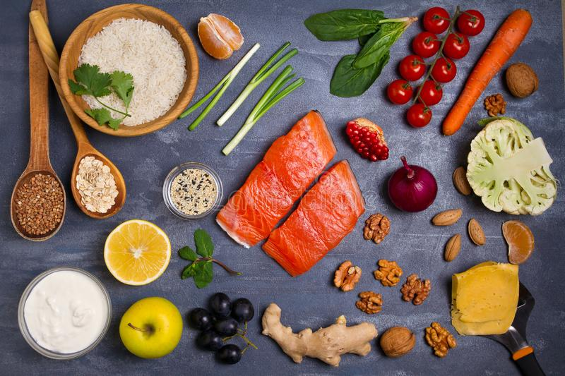 Flatlay setting of healthy food: fish salmon, bowl of rice, avocado, fruits and vegetables. royalty free stock images
