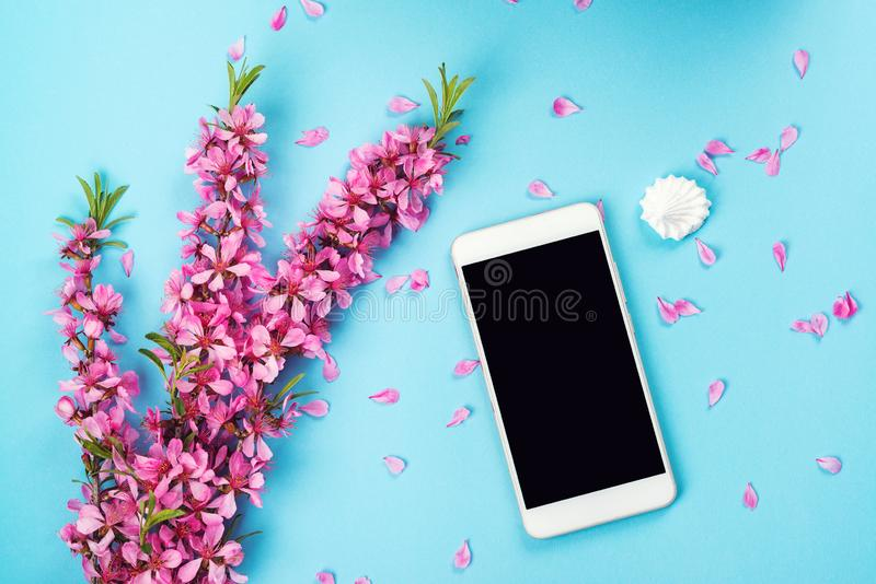 Flatlay with smartphone mock up and flowers. Floral pattern at blue background. Top view. Flowers composition. Spring background. With mobile phone. Copy space royalty free stock photo