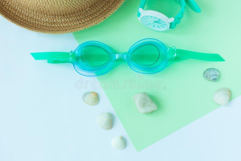 Flatlay sommar med skyddsglasögon, hatten, klockan på mintkaramellen och ljust för watersport - blå bakgrund, minimalistic stil,  arkivbilder