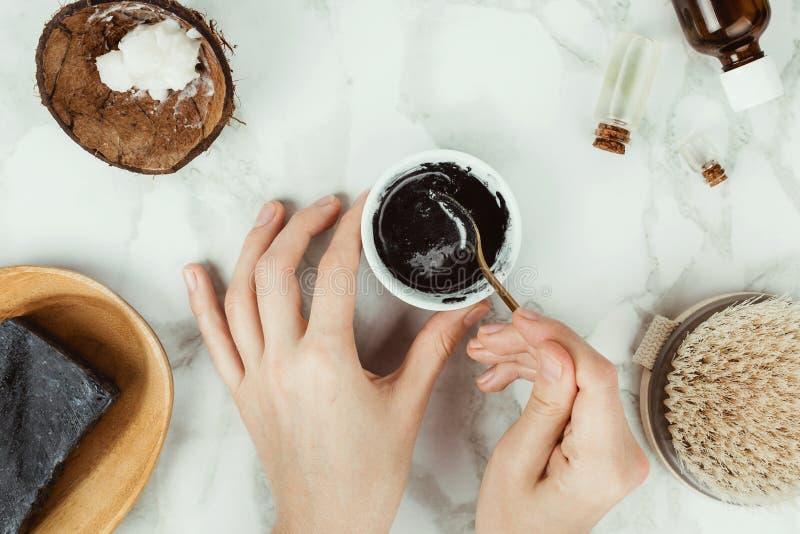 Flatlay van de handen die van de vrouw eigengemaakte houtskoolzeep met de ingrediënten aan de kant voorbereiden stock foto's