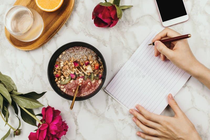 Flatlay van de handen van de vrouw met notitieboekje en smartphone, veganist smoothie werpt met chiapudding op marmer stock afbeeldingen