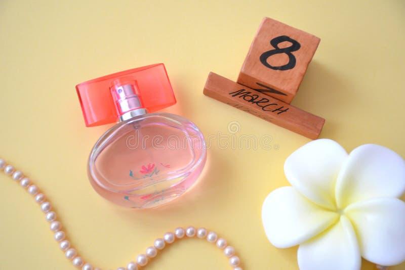 Flatlay van kalender van 8 Maart, parels maakte van natuurlijke overzeese roze parels, witte bloem en een fles parfum op gele ach royalty-vrije stock fotografie