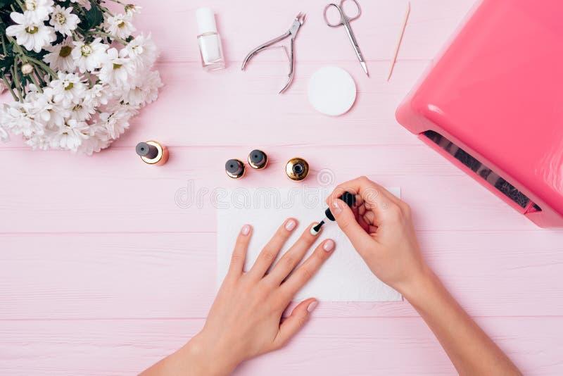 Flatlay van vrouwelijke handen past het behandelen van schellak tijdens manicure p toe royalty-vrije stock afbeeldingen