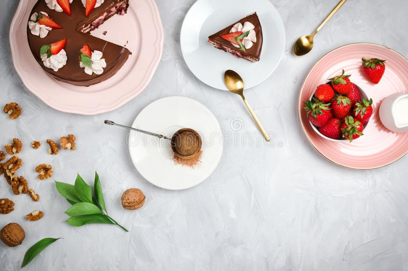 Flatlay with vegan chocolate cake, strawberries, walnuts, cocoa and other dessert ingredients. On cement background with copyspace stock image