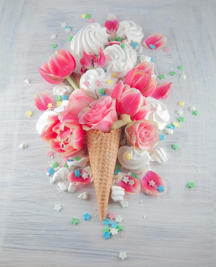 Flatlay waffle sweet ice cream cone with pink tulips and roses blossom flowers over white wood background, top view. Spring or summer mood concept stock photography