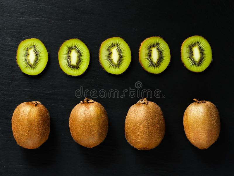 Flatlay with whole and sliced kiwi on black rustic background. stock photo