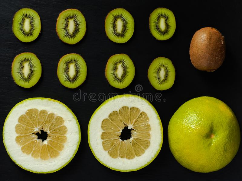 Flatlay with whole and sliced kiwi and sweetie on black rustic background. royalty free stock image