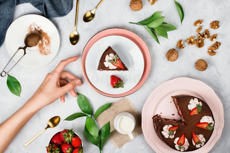 Woman`s hand reaching for a piece of vegan chocolate cake surrounded by walnuts, strawberries, cocoa powder and other dessert ing. Flatlay with woman`s hand stock image