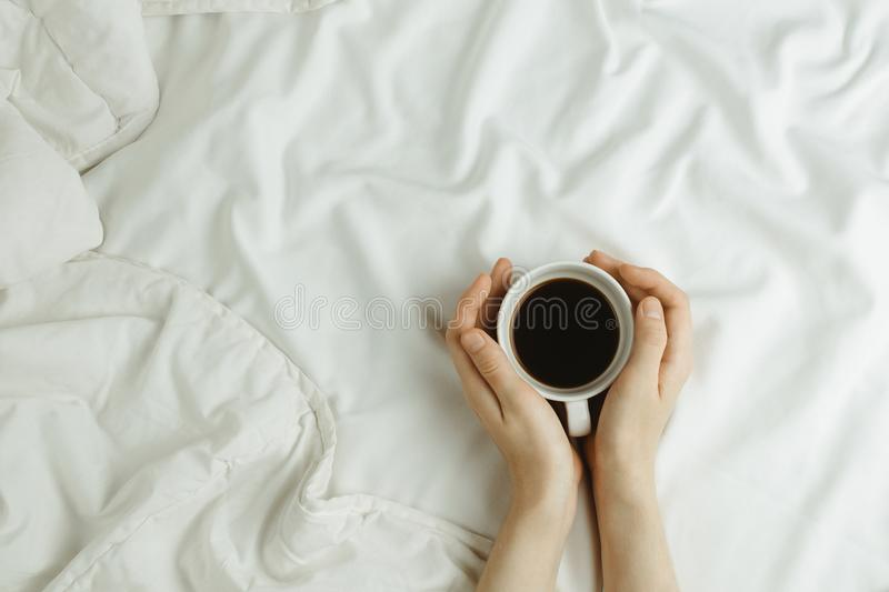 Flatlay of woman`s hands holding cup of coffee in bed on white sheets stock photos