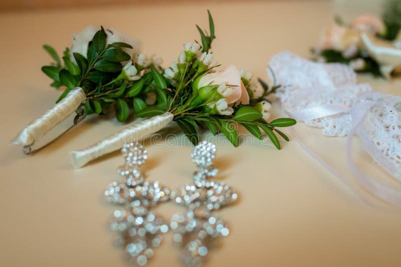 Flatlayout von Hochzeit Ohrringen, Strumpfband und Boutonniere stockfotos