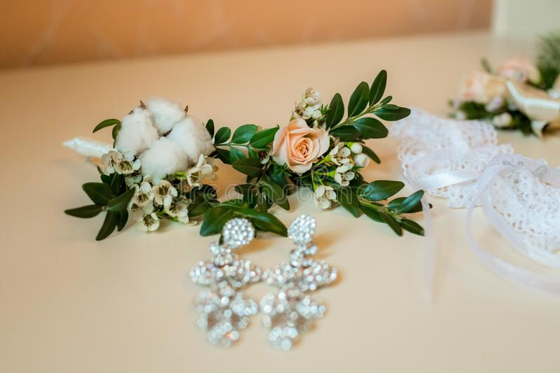 Flatlayout of wedding earrings, garter and boutonniere stock images