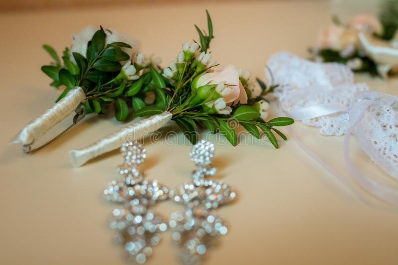 Flatlayout of wedding earrings, garter and boutonniere stock photos