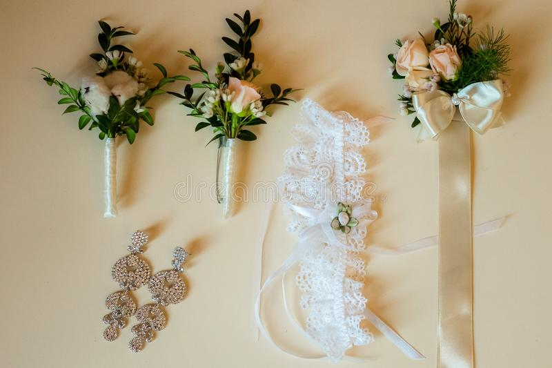 Flatlayout of wedding earrings, garter and boutonniere royalty free stock photo