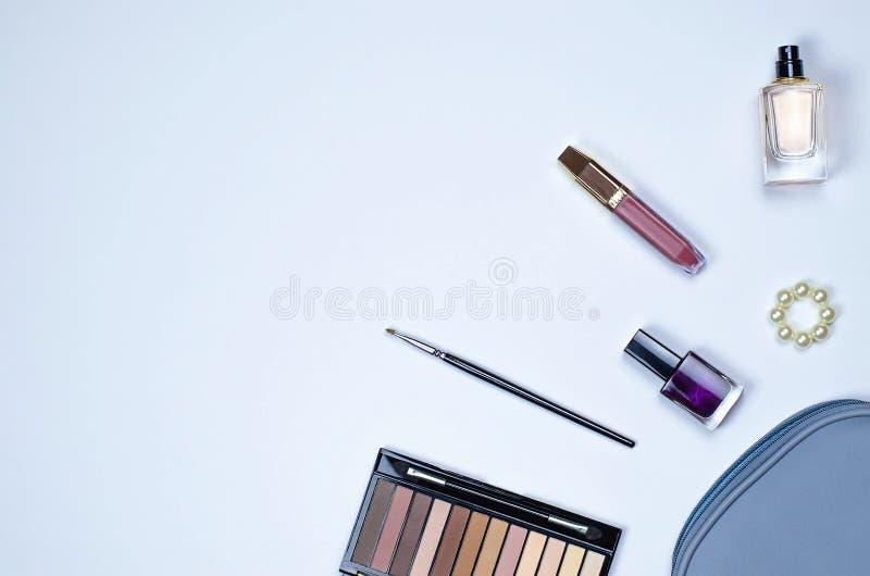Flatley av kvinnliga skönhetsmedel och kosmetiska påsar på en grå bakgrund royaltyfri bild