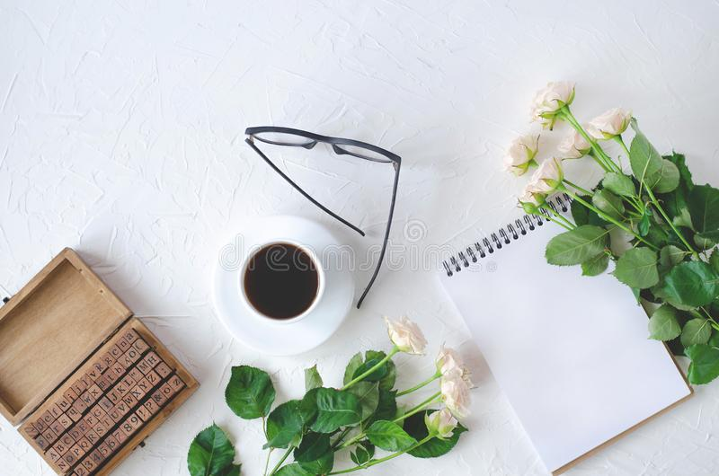 Flatley com um caderno, um café, uns vidros, uma guarda-joias e umas flores foto de stock