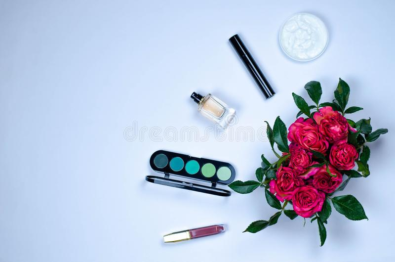 Flatley from decorative and care cosmetics and composition of fresh flowers. Eye shadow, mascara, lipstick, face cream and perfume royalty free stock photo