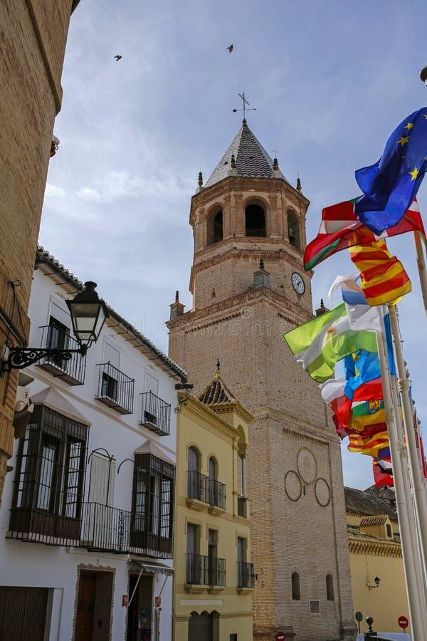 Flatternde Flaggen und Kirche von San Juan Bautista in Velez-Màlaga, Spanien lizenzfreie stockbilder