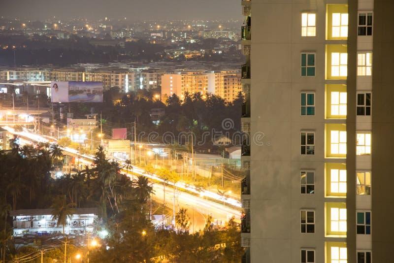Flatvensters bij nacht met Aziatische cityscape van Bangkok op de achtergrond Het verkeer en de bloeiende impuls van de stad kunn royalty-vrije stock fotografie