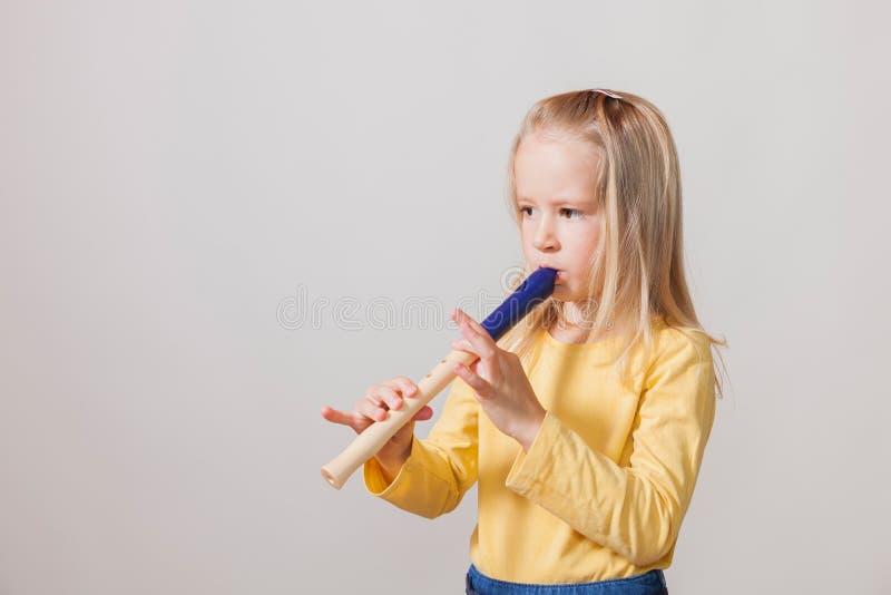Flauta practicante de la muchacha rubia foto de archivo