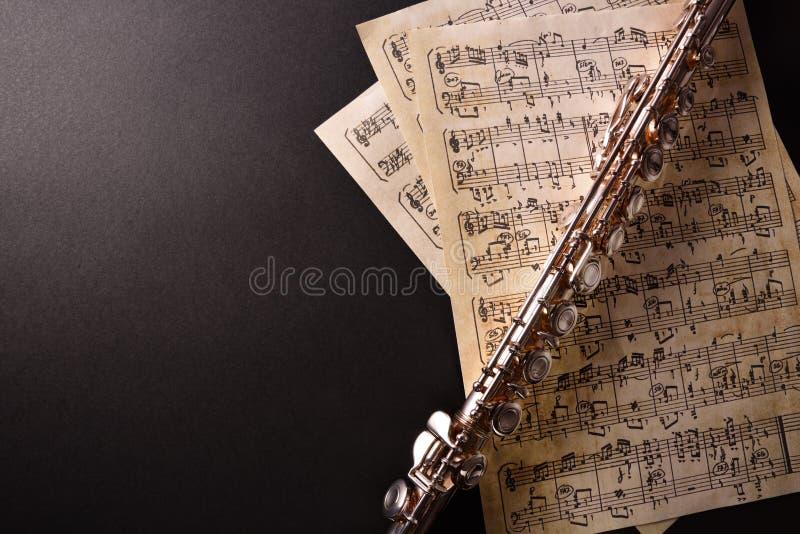 Flauta transversal y vieja partitura en la opinión de sobremesa negra fotografía de archivo libre de regalías