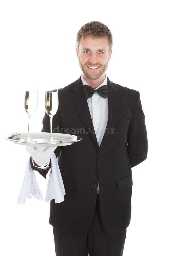 Flautas de champanhe levando do garçom seguro na bandeja fotos de stock