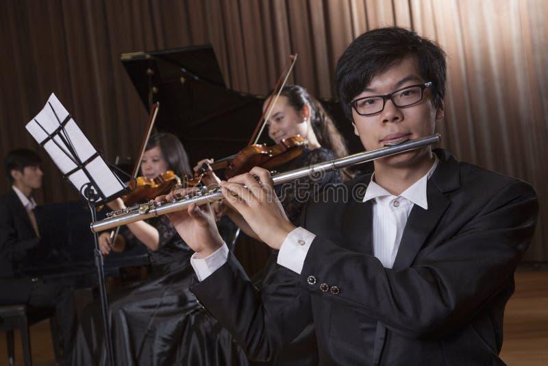 Flautista que guardara e que joga a flauta durante um desempenho, olhando a câmera fotografia de stock royalty free