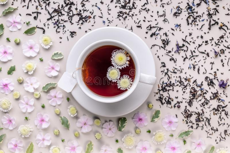 Flavored herbal tea in a white ceramic cup with a saucer. Floral pattern on a beige background. Flower tea concept. Tea bag. Top royalty free stock images