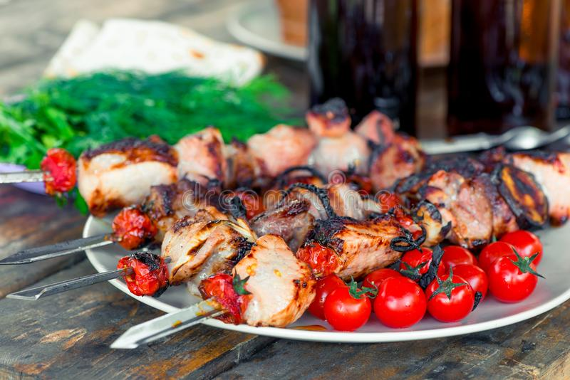 Flavored pork shish kebab with vegetables on skewers close-up on royalty free stock photo