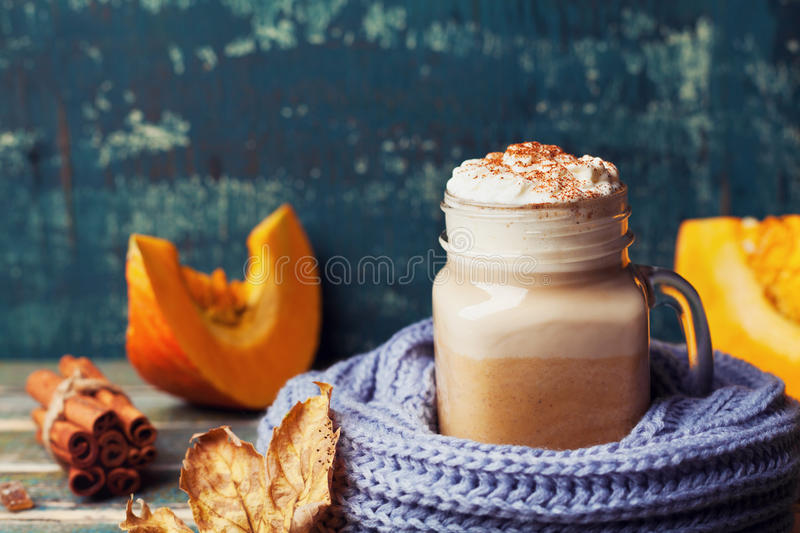 Flavored pumpkin spiced latte or coffee in cup decorated knitted scarf on teal vintage background. Autumn, fall, winter hot drink. Flavored pumpkin spiced latte royalty free stock photo