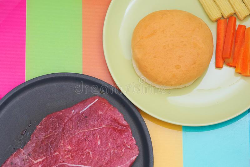 Flavored raw meat steak for cook on non stick pan with round shape or berger bread and sliced carrots with corn in plate on royalty free stock photography
