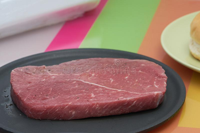Flavored raw meat steak for cook on non stick pan with round shape or berger bread in plate on colourful table,side view royalty free stock photo