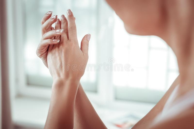 Flawless beautiful woman with tidy hands rubbing palms stock image