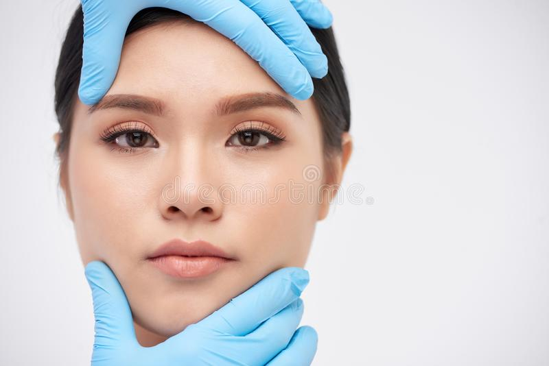 Flawless beauty. Gloved hands of surgeon on face of beautiful Vietnamese woman stock images
