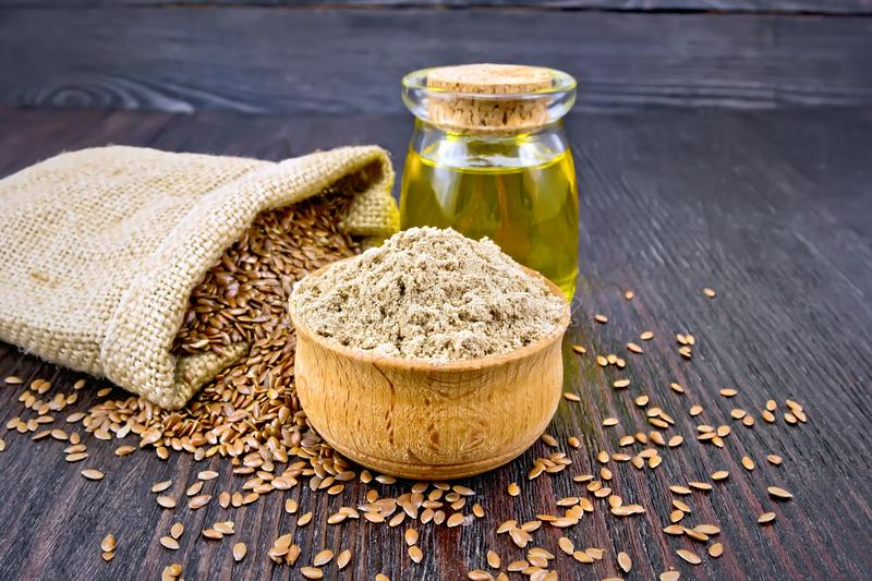 Flour linen in bowl with oil and seeds on board stock image