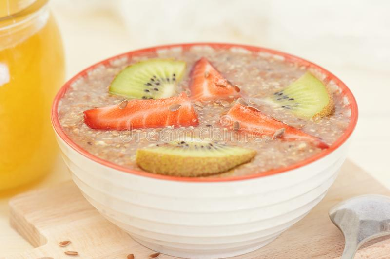 Flax seed porridge with kiwi, strawberries and honey. Healthy vegetarian breakfast. stock images