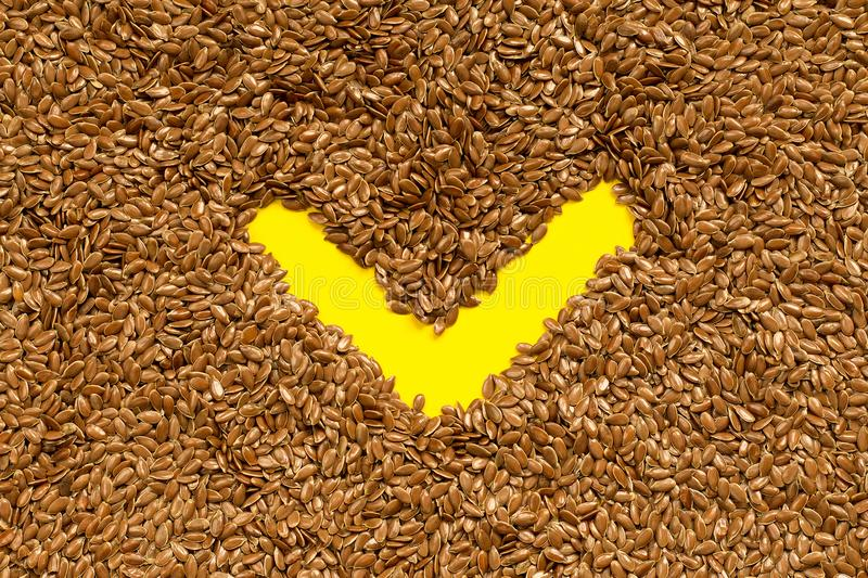 Flax seeds background with check mark symbol. Brown flax seeds background with check mark symbol stock photo