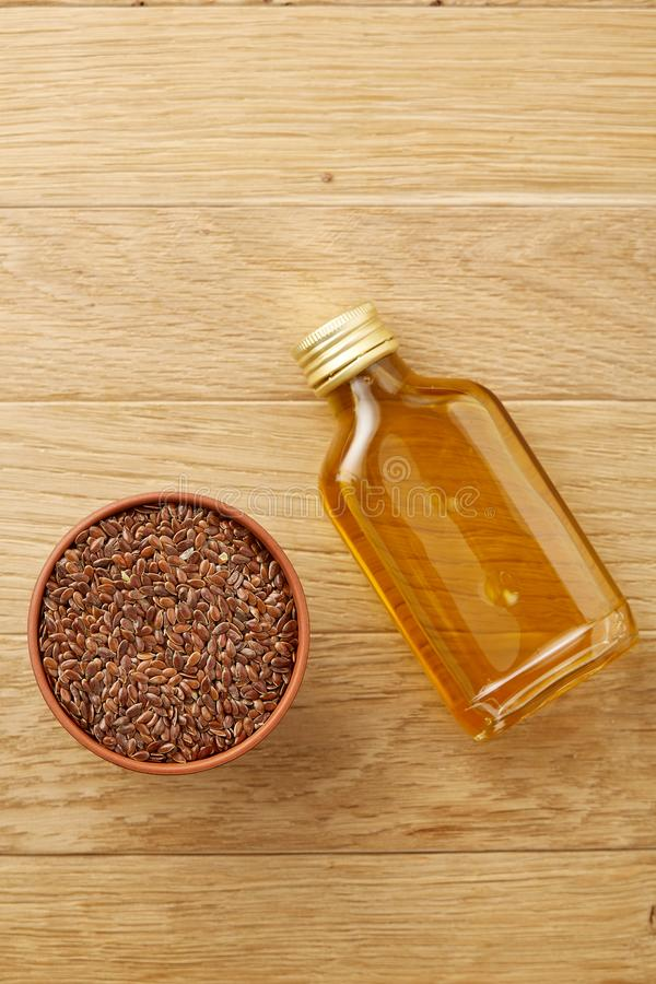 Flax seeds in bowl and flaxseed oil in glass bottle on wooden background, top view, close-up, selective focus. Brown flax seeds in wooden plate and flaxseed oil royalty free stock photos
