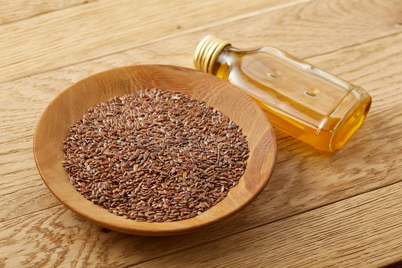 Flax seeds in bowl and flaxseed oil in glass bottle on wooden background, top view, close-up, selective focus. Brown flax seeds in wooden plate and flaxseed oil stock photo
