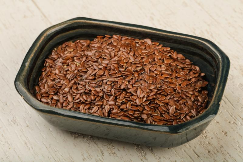 Flax seeds. Fry Flax seeds heap in the bowl over wooden background royalty free stock photo