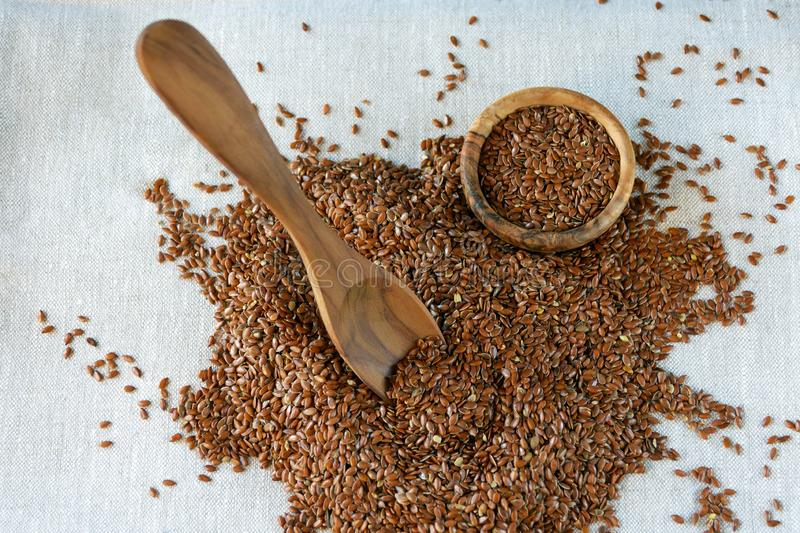 Flax seeds Linum usitatissimum - a useful and medicinal product. Close-up. Spoon and plate of natural olive tree among flax seeds. Product for beauty and royalty free stock images