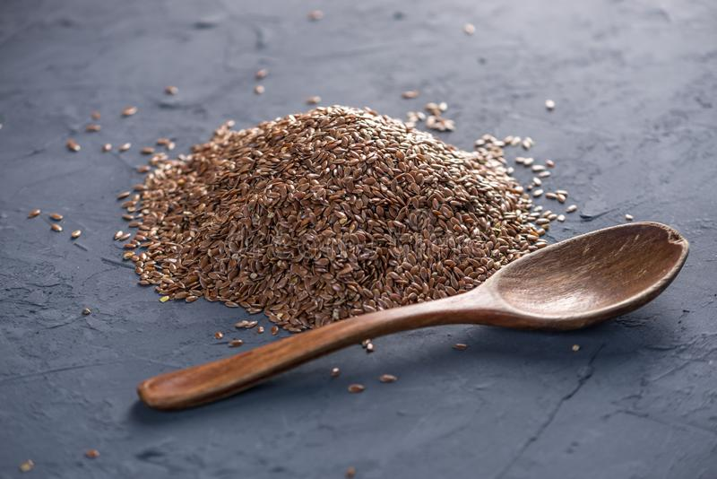 Flax seeds in a pile with spoon on a dark background. Healthy diet with omega 3 fatty acids. Flax seeds in a pile with spoon on a dark background. Concept royalty free stock photos