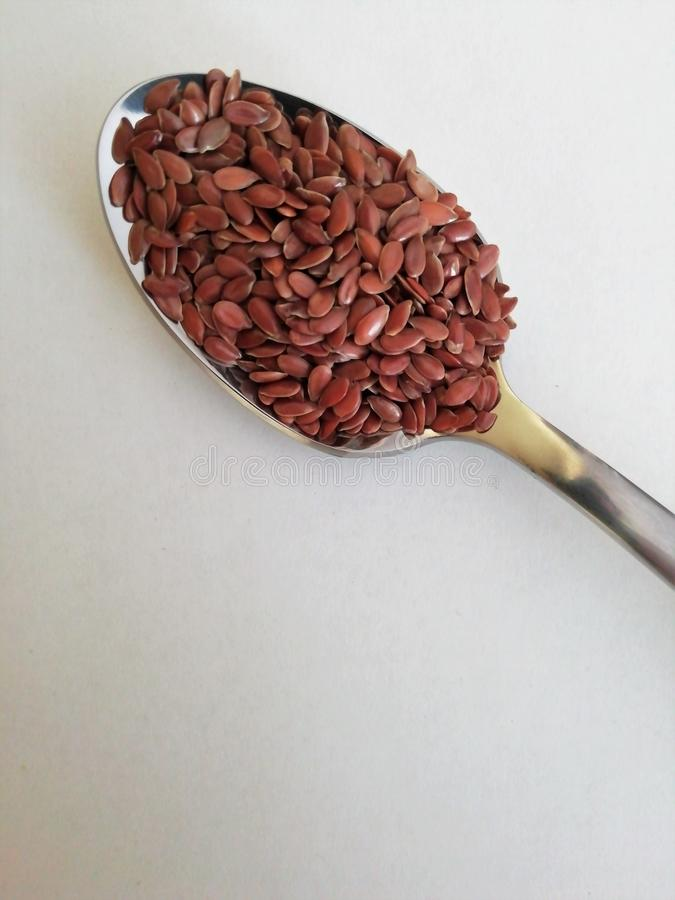 Flax seeds in the spoon on white background, vintage color tone royalty free stock photography