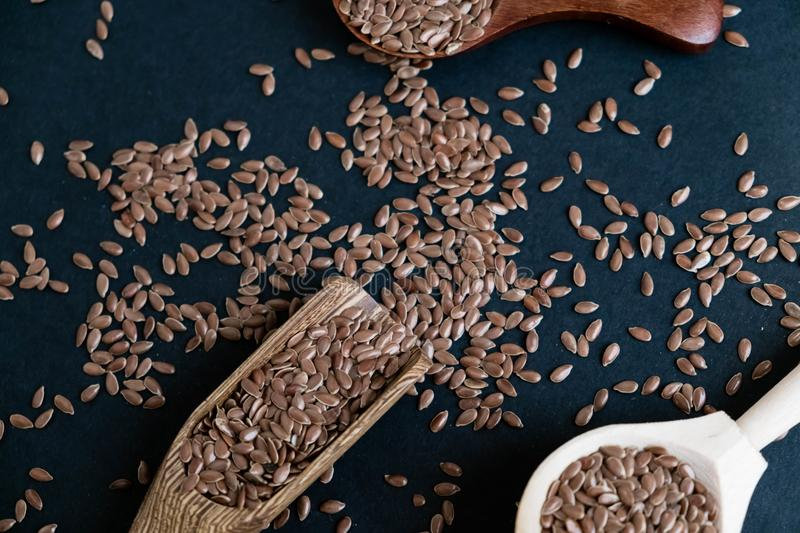Flax seeds in spoons over dark background. Natural light. Selective focus. Close up on a black background. Top view royalty free stock image