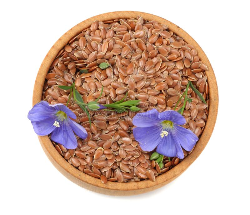 Flax seeds in wooden bowl with flower isolated on white background. flaxseed or linseed. Cereals. top view royalty free stock photography
