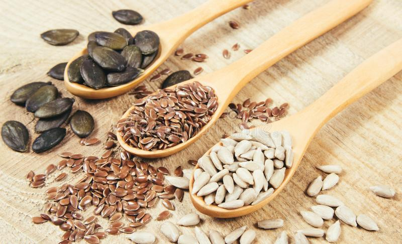 Flaxseed, κολοκύθας και ηλίανθων σπόροι στα ξύλινα κουτάλια στοκ εικόνα με δικαίωμα ελεύθερης χρήσης