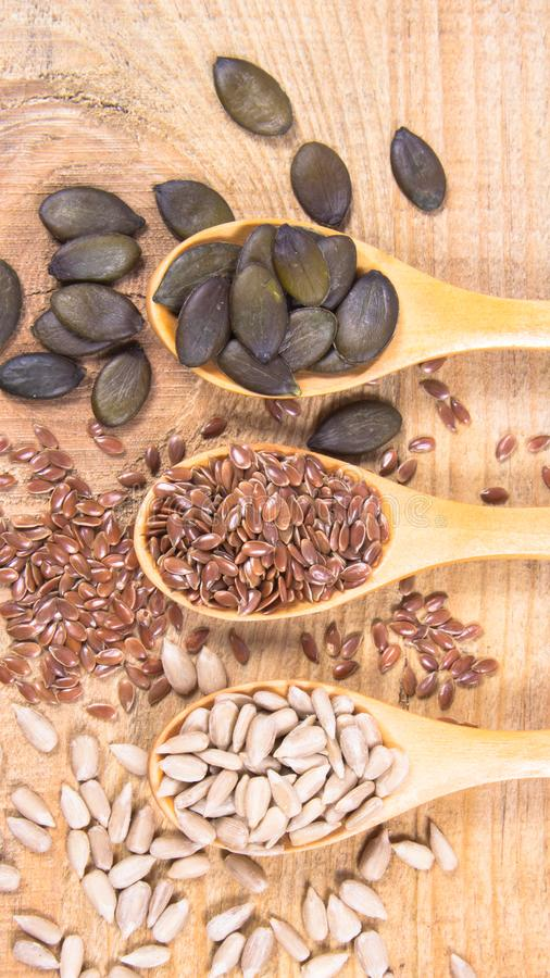 Flaxseed, κολοκύθας και ηλίανθων σπόροι στα ξύλινα κουτάλια στοκ φωτογραφίες με δικαίωμα ελεύθερης χρήσης