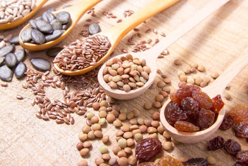 Flaxseed, κολοκύθα, σταφίδες, φακές και σπόροι ηλίανθων στα ξύλινα κουτάλια στοκ φωτογραφία