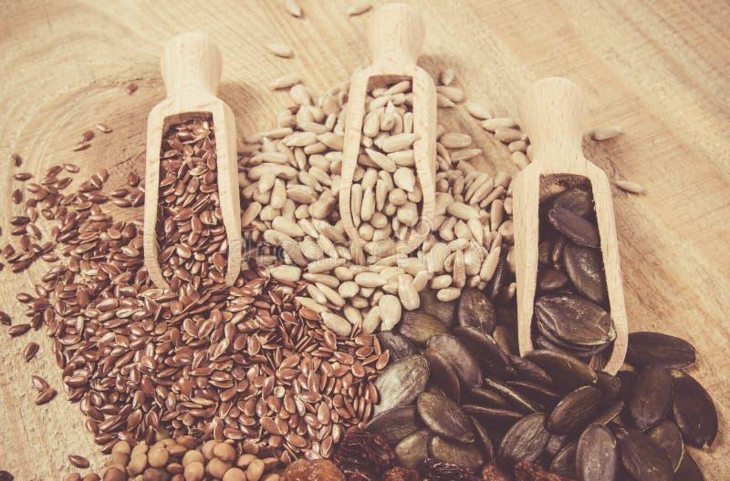 Flaxseed, κολοκύθα, σταφίδες, φακές και σπόροι ηλίανθων στα ξύλινα κουτάλια στοκ εικόνα με δικαίωμα ελεύθερης χρήσης